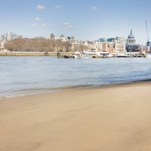 a calm view of the city of london from an empty thames beach on the south embankment